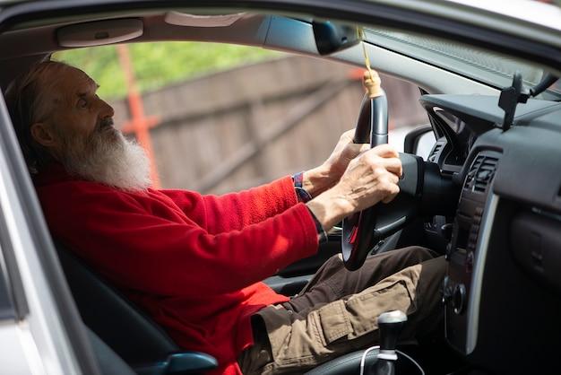Retired elder senior  man with long beard driving car
