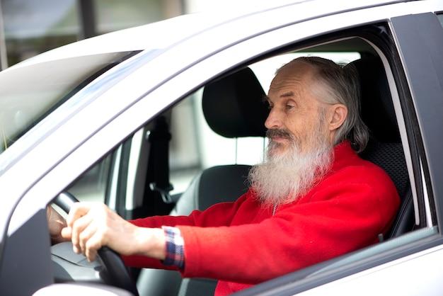 Retired elder senior man with long beard driving gray car