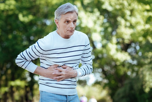 Retired frustrated unhappy man touching his belly and expressing frustration while suffering from stomachache outdoors