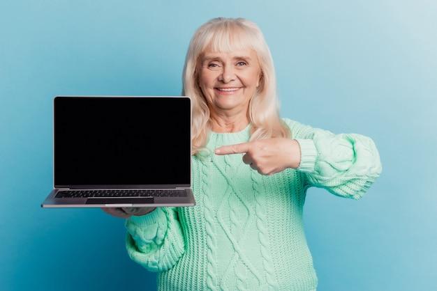 은퇴한 할머니 홀드 노트북 쇼 포인트 손가락 디스플레이 파란색 배경에 고립