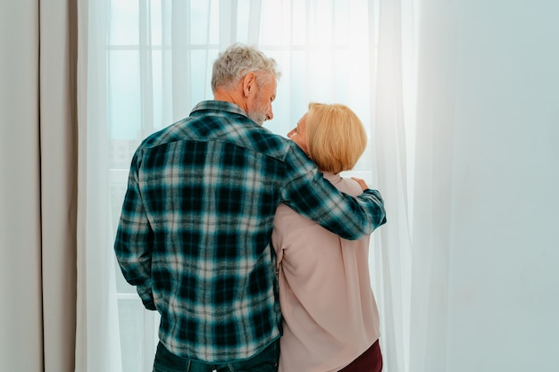 은퇴한 남편과 아내가 집에서 서로 포옹