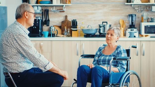 휠체어를 탄 은퇴한 여성이 부엌에서 노부부와 대화를 나누고 있습니다. 아내와 이야기 하는 노인. 보행 장애가 있는 장애인과 함께 생활
