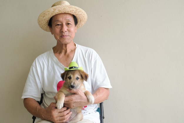 Retired male senior sitting on chair holding little puppy dog