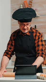 Uomo in pensione che segue consigli culinari su tablet, impara tutorial di cucina sui social media, forma l'impasto con il mattarello di legno. nonno con bonete e grembiule utilizzando il computer portatile che prepara torte fatte in casa