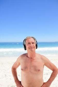 해변에서 일부 음악을 듣고 은퇴 한 남자