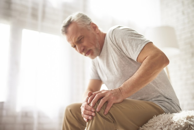 Retired man pensioner suffering knee pain at home.