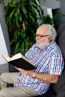 Retired man reading a book in his home