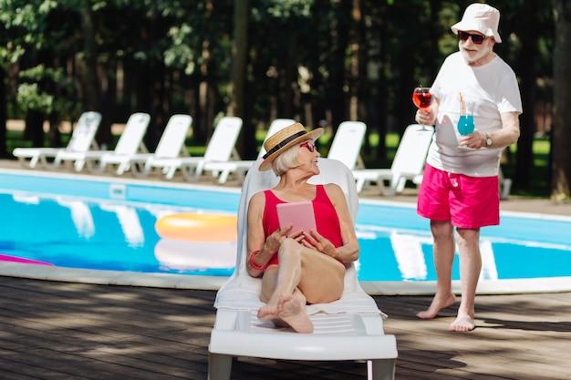 Пенсионер в красных шортах и темных солнцезащитных очках приносит коктейли своей стильной современной жене