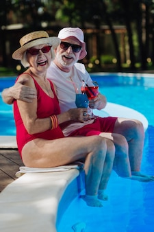 Retired man and woman holding glasses with cocktail spending holiday near the pool