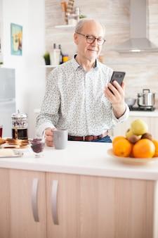 朝食を食べながらキッチンでスマートフォンでビデオを見ている引退した老人。朝食時に朝のコーヒーを楽しみながら、最新のテクノロジーを使用しています。引退したセンの本物の肖像画