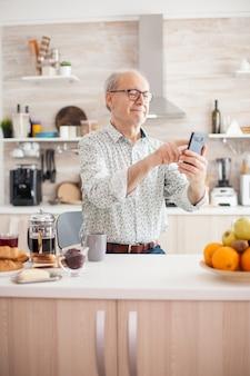 朝食時にキッチンでインターネットとスマートフォンを使用して、電話でスクロールする引退した老人。インターネットオンラインチャット技術を使用している高齢者ビデオウェブカメラがビデオ通話接続を行っているc
