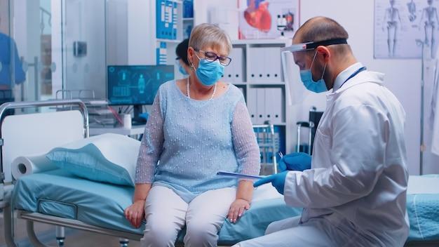 Пожилая женщина на пенсии в защитной маске расписывается для выписки. современная частная больница или клиника. консультация врача-терапевта во время глобального кризиса covid-19, проблемы здравоохранения