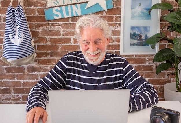 Дед на пенсии матрос с помощью портативного компьютера для видеозвонка внуку. с белыми волосами счастливый пожилой мужчина наслаждается технологиями и общением. кирпичная стена на заднем плане и украшения