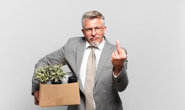 Пенсионер старший бизнесмен чувствует себя злым, раздраженным, мятежным и агрессивным, щелкает средним пальцем, сопротивляется