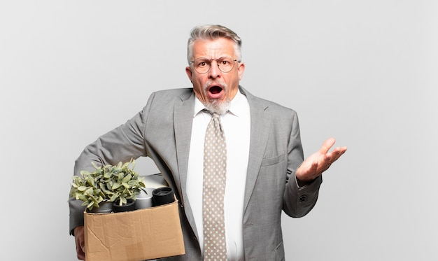 引退したシニアビジネスマンは、ストレスと恐怖の表情で、非常にショックを受け、驚き、不安とパニックを感じています