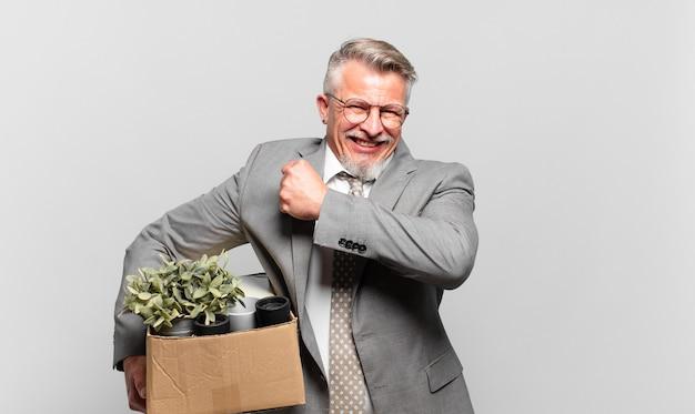挑戦に直面したり、良い結果を祝ったりするときに、幸せで、前向きで、成功し、やる気を感じている引退したシニアビジネスマン