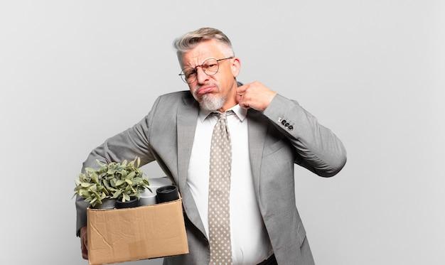 Пенсионер старший бизнесмен чувствует стресс, тревогу, усталость и разочарование, дергает за шею рубашки, выглядит разочарованным из-за проблемы