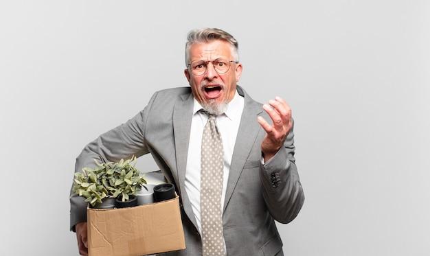 必死になって欲求不満になり、ストレスを感じ、不幸でイライラし、叫び、叫んでいる引退したシニアビジネスマン