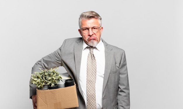 Старший бизнесмен на пенсии выглядит озадаченным и сбитым с толку, нервно прикусывает губу, не зная, как решить проблему