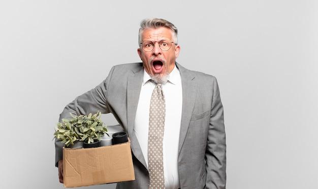 非常にショックを受けたり驚いたりして、口を開けてすごいことを言って見つめている引退したシニアビジネスマン