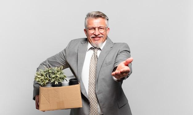 フレンドリーで自信に満ちた前向きな表情で幸せそうに笑っている退職したシニアビジネスマンは、オブジェクトやコンセプトを提供し、示しています