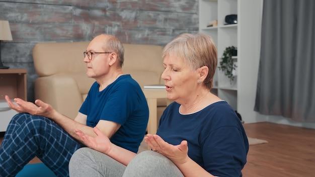 Пожилые супружеские пары делают дыхательные упражнения на коврике для йоги в гостиной. здоровый и активный образ жизни пожилого человека, упражнения и тренировки дома, тренировки и фитнес для пожилых людей