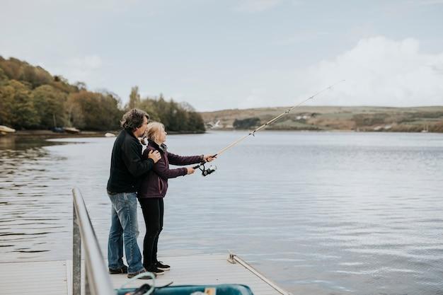 Пожилая пара на пенсии, наслаждающаяся активным отдыхом на рыбалке
