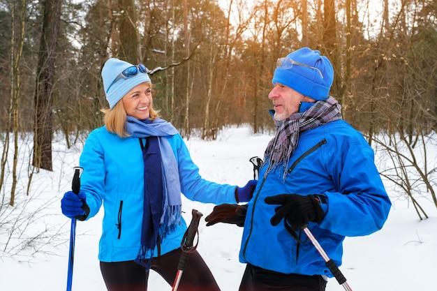 은퇴 한 노인 부부 휴식과 눈 덮인 겨울 공원에서 이야기하는 재미