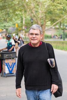 Retired senior man at park, walking and relaxing, smiling expression