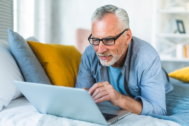 Retired senior man relaxing on bed looking at laptop