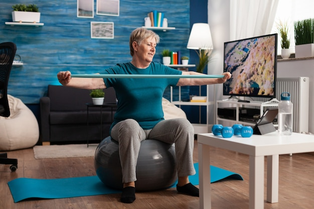 Retired senior man sitting on fitness swiss ball in living room doing wellness fitness workout streching arm muscles using aerobics elastic band