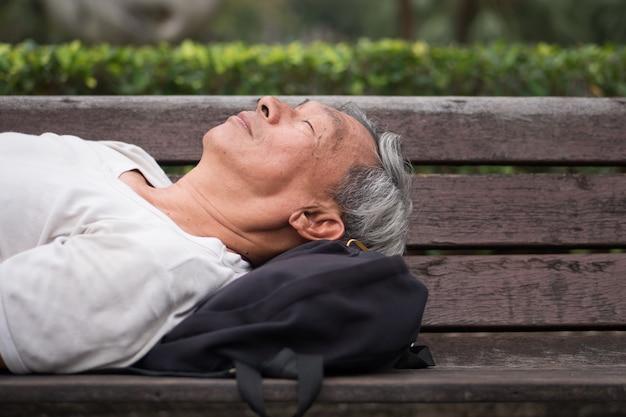 公共の公園で座っている退職したシニア男性