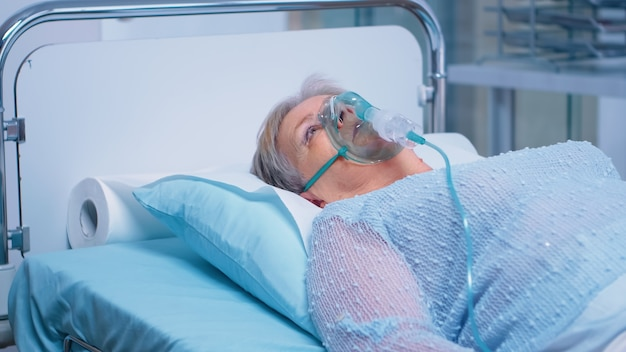 感染症の治療を受けている病院のベッドに横たわって、酸素マスクで呼吸している引退した年配の老婆。コロナウイルスcovid-19医療パンデミックヘルスケアシステム