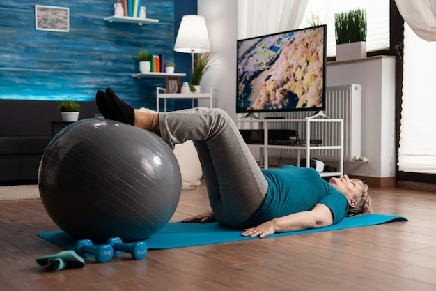 居間でヨガマットの上に座ってスイスボールを使用してレッグアップ運動を練習している引退した年配の女性