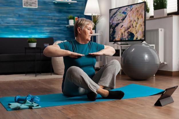 Пенсионерка старшая женщина ест учебник по фитнесу на ноутбуке, сидя на коврике для йоги, растягивая руку