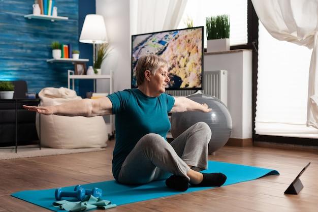 Старшая пенсионерка ищет учебник по фитнесу на ноутбуке, сидя на коврике для йоги, растягивая руку во время оздоровительной тренировки в гостиной