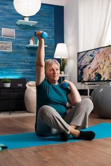 Donna anziana in pensione seduta sul tappetino da yoga nella posizione del loto alzando la mano durante la routine di benessere in fase di riscaldamento allenando i muscoli del corpo utilizzando manubri