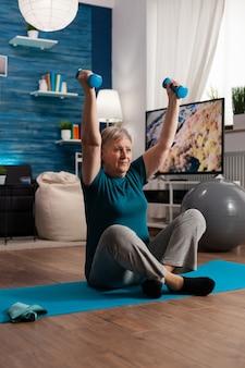 Donna anziana in pensione seduta sul tappetino da yoga nella posizione del loto alzando la mano durante la routine di benessere