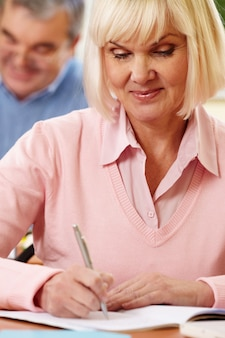 Retired woman focused on her essay