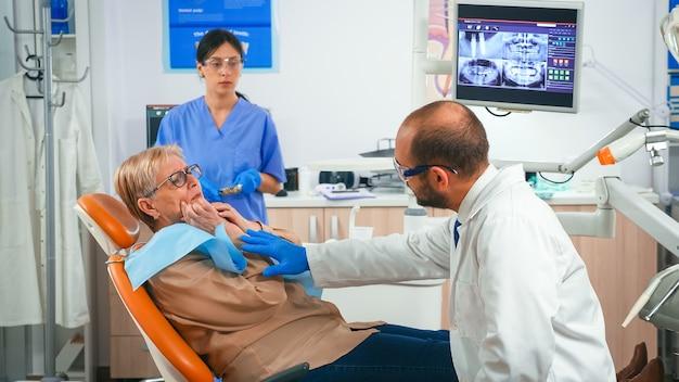 医者と話している間、頬に手を握って歯茎の痛みの症状を持っている引退した女性。看護師が滅菌ツールを準備している間、口を示す医師に歯の問題を説明する高齢の患者。