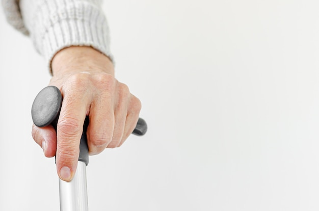 Retired woman holding metal walking stick in hand. medical and healthcare concept. copy space