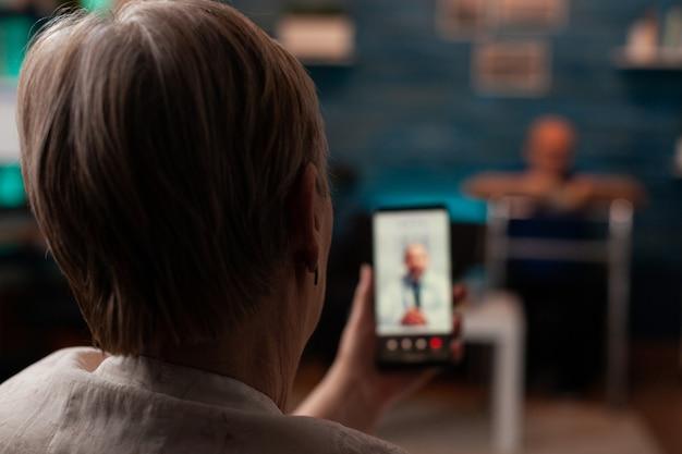 Пенсионерка, держащая смартфон с видеозвонком