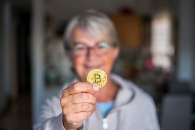 Пенсионерка, показывающая в камеру улыбающуюся монету криптовалюты - старший в очках, кавказец с биткойном на руке у себя дома в помещении - расфокусированный фон