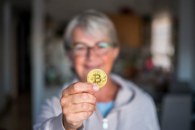 Retired woman showing at the camera a crypto currency coin smiling - senior with glasses caucasian with a bitcoin on her hand at home indoor - defocused background