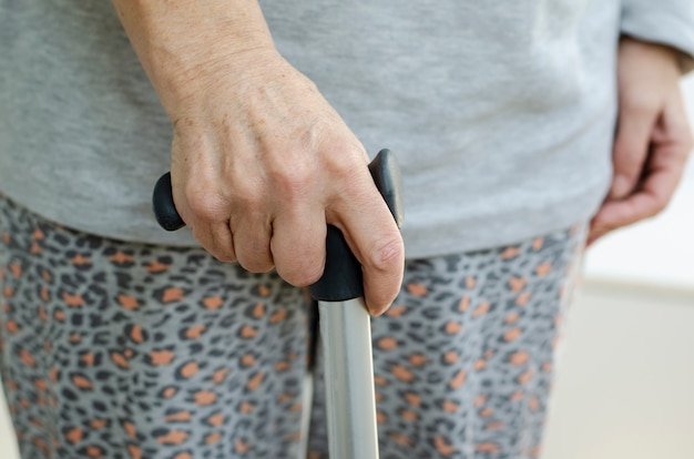 Retired woman with holding metal walking stick in hand at home