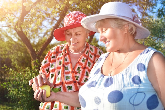 Retired women best friends in hats walk happily in the garden
