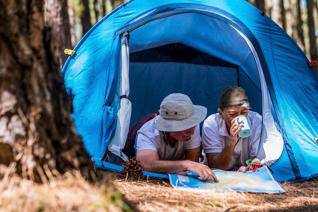 Retirement couple lifestyle enjoy travel tourism vacation laying inside a tent in free wild camping outdoor - aged people and feeling with nature woods forest experience - elderly traveler