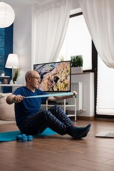 腕の筋肉を伸ばす交差した位置で脚をヨガマットに座っている退職後の年配の男性