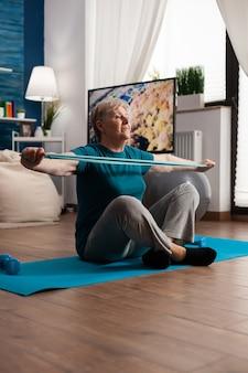 Пенсионная старшая женщина, сидящая на коврике для йоги, растягивая мышцы ног с помощью эластичной ленты