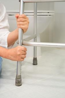 退職女性がトイレに倒れ歩行器を押さえようとする
